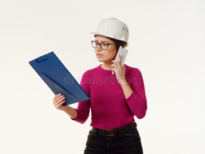 Συναισθηματικός επιστάτης κοριτσιών σε ένα κράνος σε ένα άσπρο υπόβαθρο στοκ εικόνα με δικαίωμα ελεύθερης χρήσης