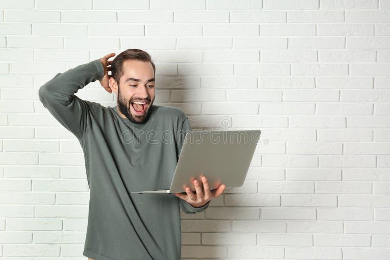 Συναισθηματικός νεαρός άνδρας με τη νίκη εορτασμού lap-top κοντά στο τουβλότοιχο στοκ φωτογραφία με δικαίωμα ελεύθερης χρήσης