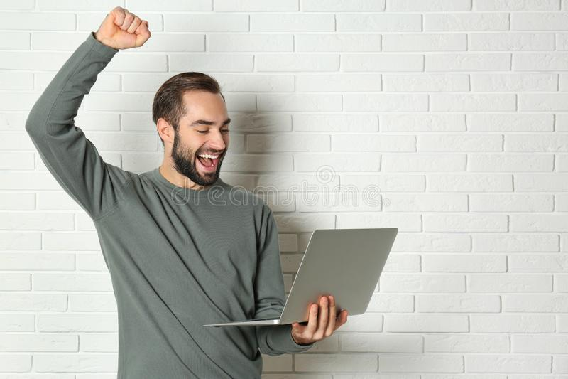 Συναισθηματικός νεαρός άνδρας με τη νίκη εορτασμού lap-top κοντά στο τουβλότοιχο στοκ εικόνα