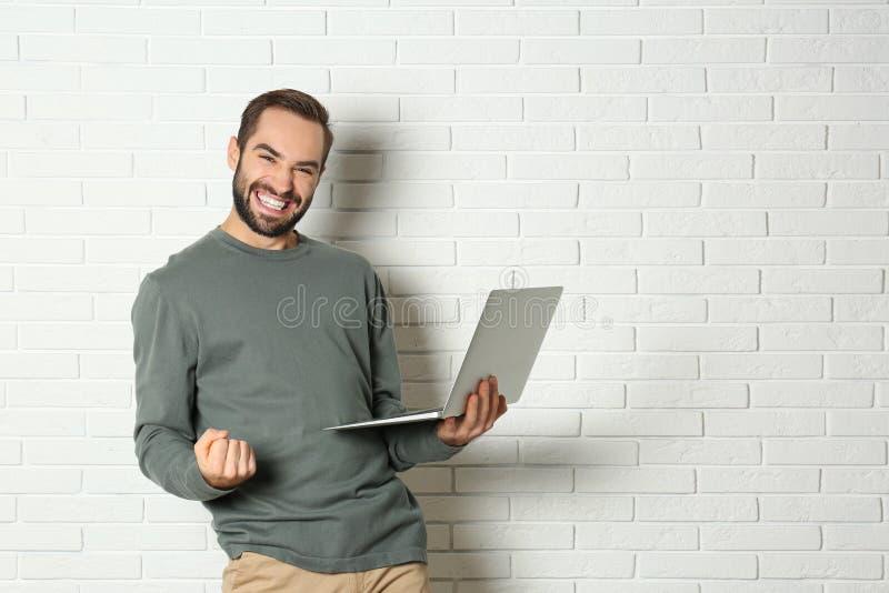 Συναισθηματικός νεαρός άνδρας με τη νίκη εορτασμού lap-top κοντά στο τουβλότοιχο στοκ εικόνες
