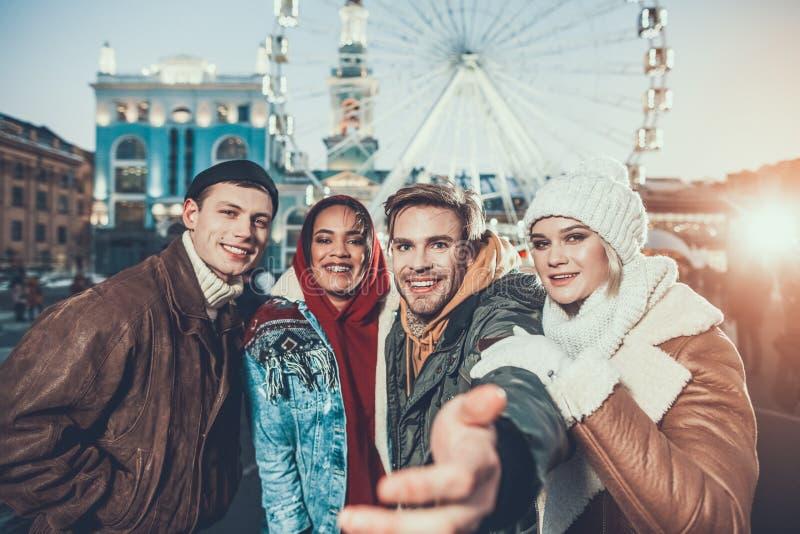Συναισθηματικό άτομο που βάζει το χέρι στη κάμερα στεμένος με τους φίλους στοκ εικόνες