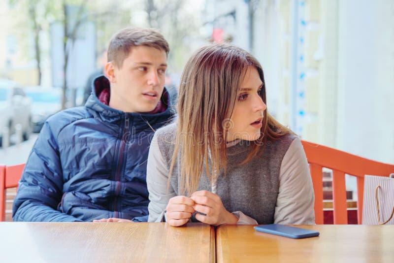 Συναισθηματικό έκπληκτο νέο ζεύγος στον υπαίθριο καφέ, που κάθεται στον πίνακα στοκ φωτογραφίες με δικαίωμα ελεύθερης χρήσης