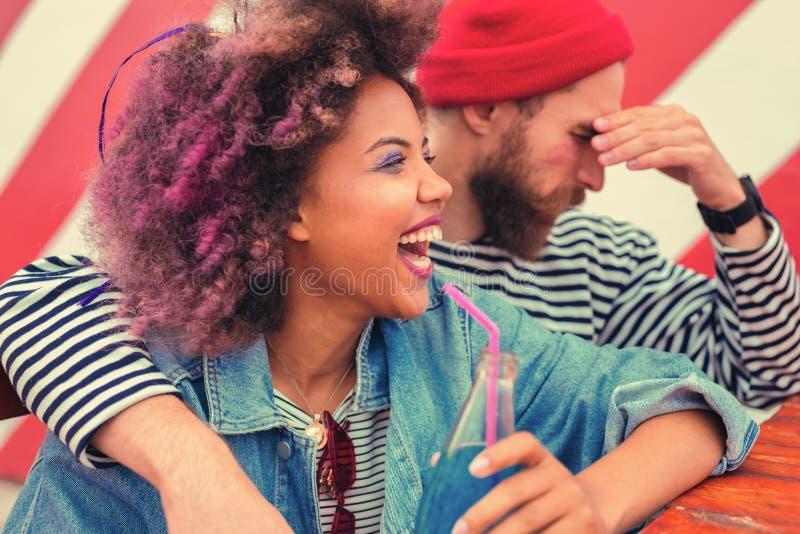 Συναισθηματικό γέλιο γυναικών και ο φίλος της που έχουν τον πονοκέφαλο μετά από το κόμμα στοκ φωτογραφία