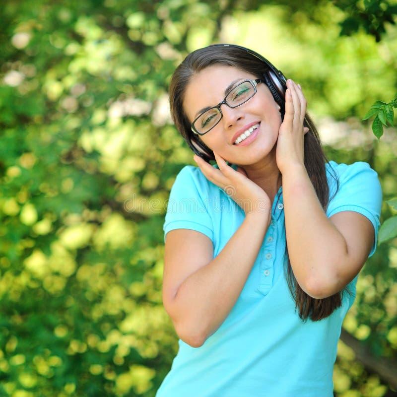 Συναισθηματικό κορίτσι ευτυχίας με τα ακουστικά που απολαμβάνει τη φύση και mus στοκ φωτογραφίες