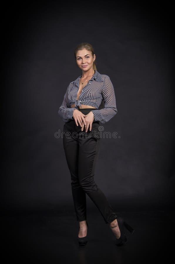 Συναισθηματικό κορίτσι σε ένα πουκάμισο και μαύρα εσώρουχα που θέτουν στο σκοτεινό υπόβαθρο στοκ φωτογραφία με δικαίωμα ελεύθερης χρήσης