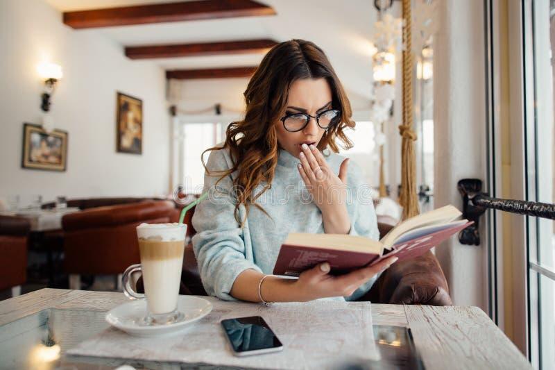 Συναισθηματικό κορίτσι στα γυαλιά που διαβάζει το βιβλίο στον καφέ στοκ φωτογραφίες με δικαίωμα ελεύθερης χρήσης