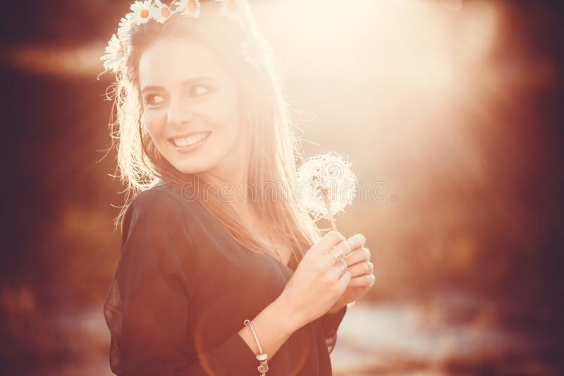 Συναισθηματικό νέο κορίτσι με τις μεγάλες πικραλίδες διαθέσιμες και με ένα στεφάνι των μαργαριτών στο κεφάλι της στο εκλεκτής ποι στοκ φωτογραφία με δικαίωμα ελεύθερης χρήσης