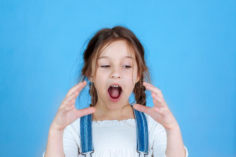 Συναισθηματικό πορτρέτο λίγο όμορφο κορίτσι με τις πλεξίδες στις φόρμες τζιν που τρώει τα δαγκώματα που κρατούν ένα μήλο 6-7 στού στοκ φωτογραφίες