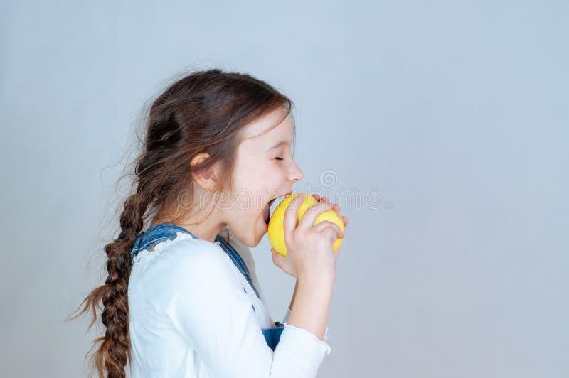 Συναισθηματικό πορτρέτο λίγο όμορφο κορίτσι με τις πλεξίδες στις φόρμες τζιν που τρώει τα δαγκώματα που κρατούν ένα μήλο 6-7 στού στοκ εικόνα με δικαίωμα ελεύθερης χρήσης