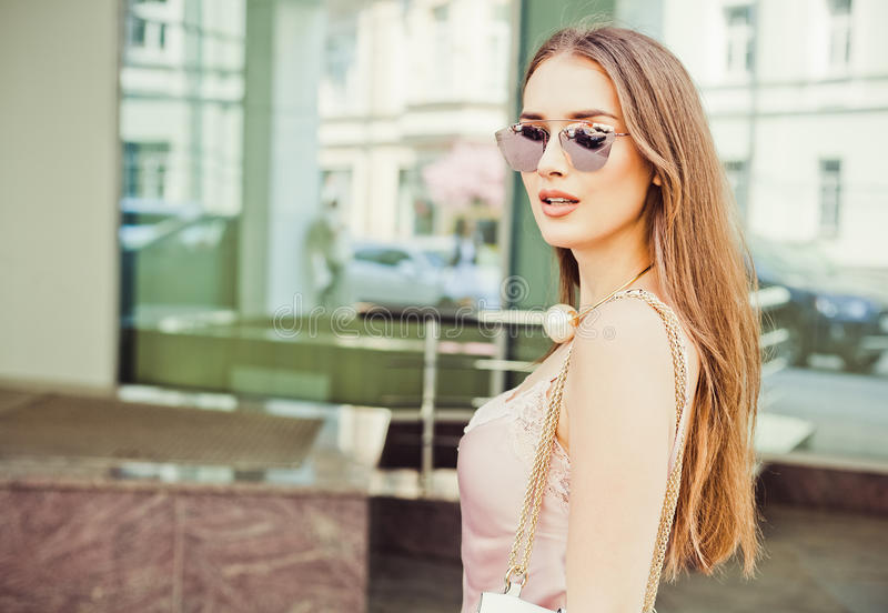 Συναισθηματικό πορτρέτο μιας όμορφης νέας γυναίκας brunette με μακρυμάλλη σε ένα μοντέρνο φόρεμα και τα γυαλιά ηλίου στοκ φωτογραφία με δικαίωμα ελεύθερης χρήσης