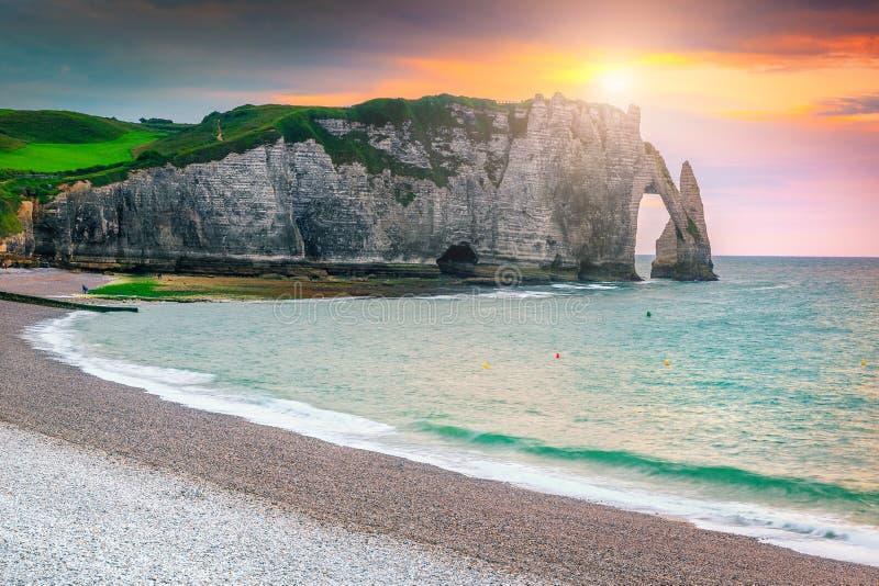 Συναρπαστική παραλία και μαγικό ζωηρόχρωμο ηλιοβασίλεμα Etretat, Νορμανδία, Γαλλία αμμοχάλικου στοκ φωτογραφία