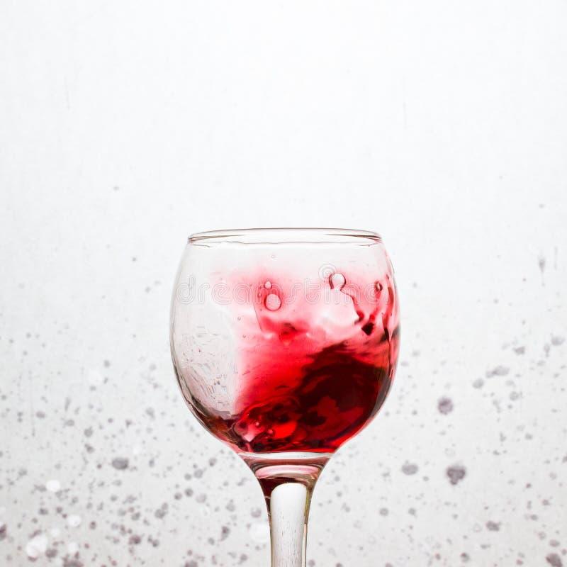 Συναρπαστικός παφλασμός του κόκκινου κρασιού σε ένα γυαλί σε ένα γκρίζο αφηρημένο υπόβαθρο στοκ φωτογραφία με δικαίωμα ελεύθερης χρήσης