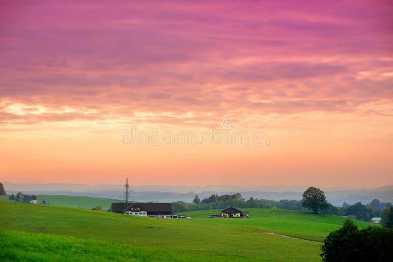 Συναρπαστικό lansdcape της αυστριακής επαρχίας στο ηλιοβασίλεμα Δραματικός ουρανός πέρα από τους ειδυλλιακούς πράσινους τομείς τω στοκ εικόνες