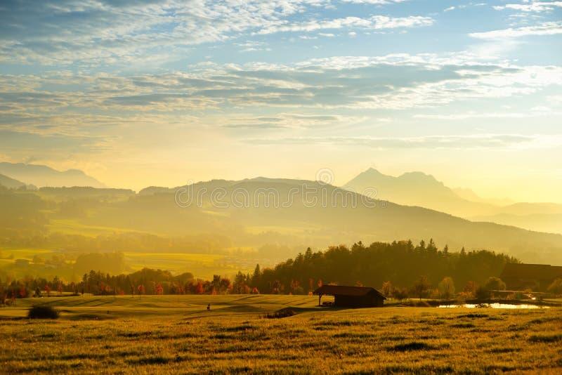 Συναρπαστικό lansdcape της αυστριακής επαρχίας στο ηλιοβασίλεμα Δραματικός ουρανός πέρα από τους ειδυλλιακούς πράσινους τομείς τω στοκ φωτογραφία με δικαίωμα ελεύθερης χρήσης