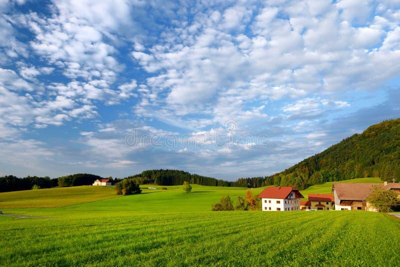 Συναρπαστικό lansdcape της αυστριακής επαρχίας στο ηλιοβασίλεμα Δραματικός ουρανός πέρα από τους ειδυλλιακούς πράσινους τομείς τω στοκ φωτογραφία