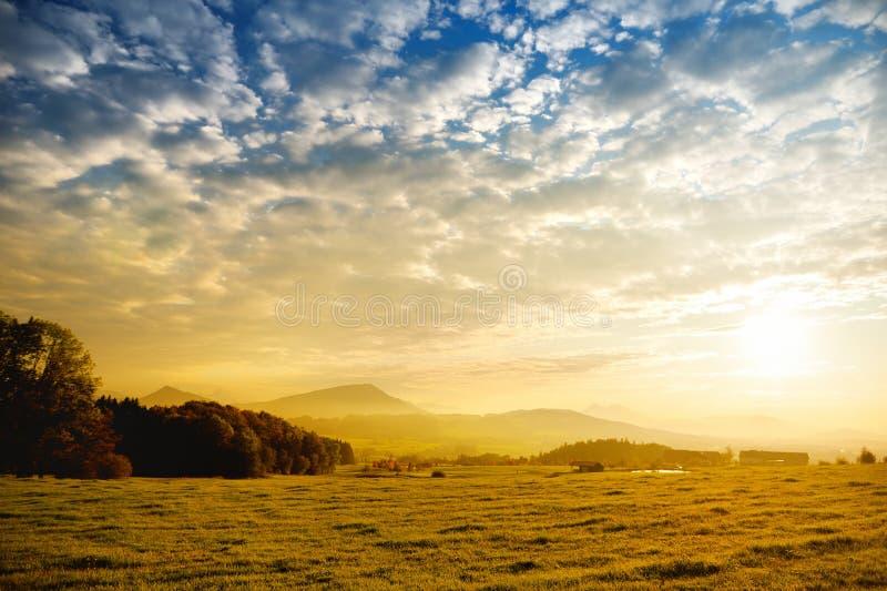 Συναρπαστικό lansdcape της αυστριακής επαρχίας στο ηλιοβασίλεμα Δραματικός ουρανός πέρα από τους ειδυλλιακούς πράσινους τομείς τω στοκ εικόνες με δικαίωμα ελεύθερης χρήσης
