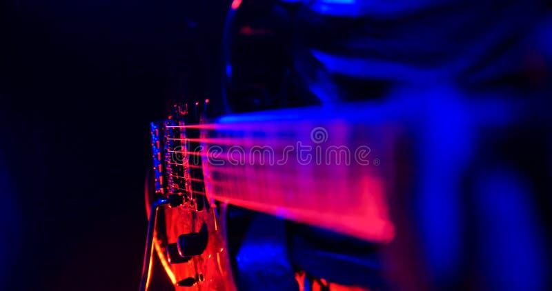Συναυλία βράχου Ο κιθαρίστας παίζει την κιθάρα E Εστίαση στις σειρές στοκ φωτογραφία