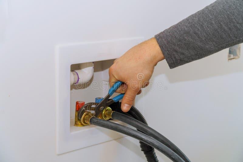 συνδέοντας μάνικα παροχής νερού στο πλυντήριο που χρησιμοποιεί το γαλλικό κλειδί στοκ φωτογραφίες