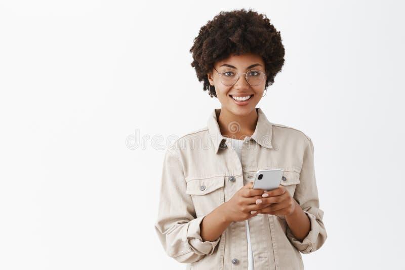Συνδεμένος με τον κόσμο παντού Εσωτερικός πυροβολισμός της ελκυστικής ευτυχούς και ικανοποιημένης χρησιμοποίησης γυναικών αφροαμε στοκ φωτογραφία με δικαίωμα ελεύθερης χρήσης