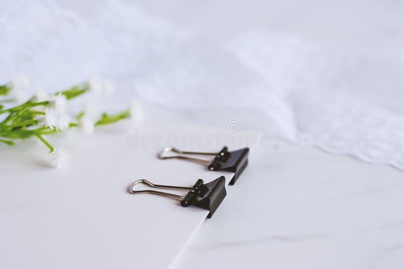 Συνδετήρας συνδέσμων που δεσμεύει την κάρτα της Λευκής Βίβλου με το διακοσμητικό λουλούδι και στοκ φωτογραφία