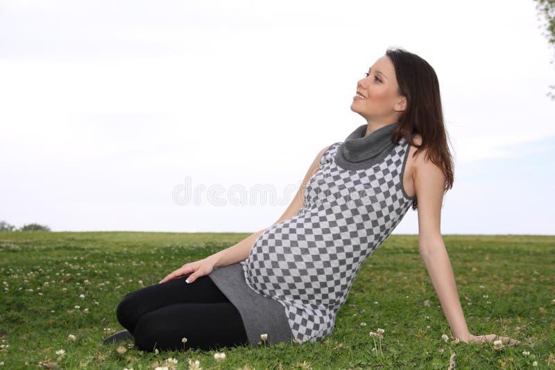 Συνεδρίαση έγκυων γυναικών σε έναν χορτοτάπητα στοκ φωτογραφίες