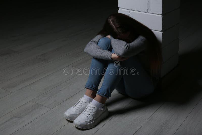 Συνεδρίαση έφηβη στη στήλη στο εσωτερικό στοκ φωτογραφία με δικαίωμα ελεύθερης χρήσης