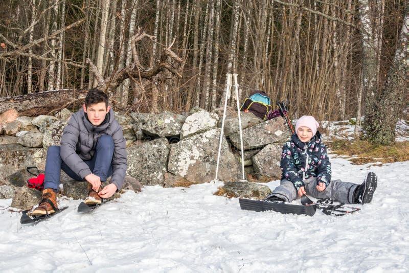 Συνεδρίαση αγοριών και κοριτσιών στο χιόνι που βάζει στα σκι τους ενάντια σε έναν τοίχο πετρών στοκ εικόνες