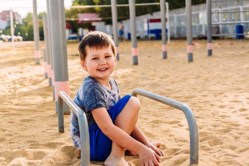 Συνεδρίαση αγοριών χαμόγελου 5χρονη στην κίτρινη άμμο στην παραλία στοκ εικόνα με δικαίωμα ελεύθερης χρήσης