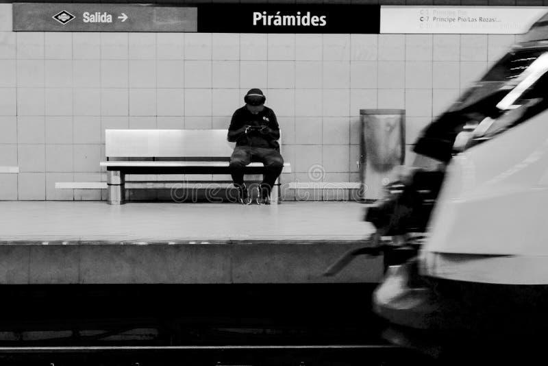 Συνεδρίαση ατόμων σε έναν πάγκο με ένα τραίνο που ταξιδεύει κατά μήκος της πλατφόρμας στοκ εικόνα με δικαίωμα ελεύθερης χρήσης