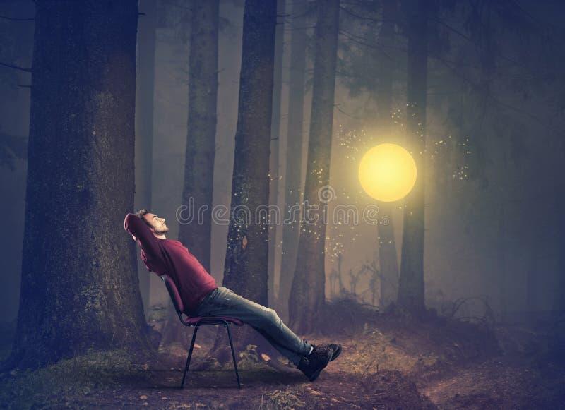 Συνεδρίαση ατόμων στην καρέκλα στο δάσος στοκ εικόνα με δικαίωμα ελεύθερης χρήσης