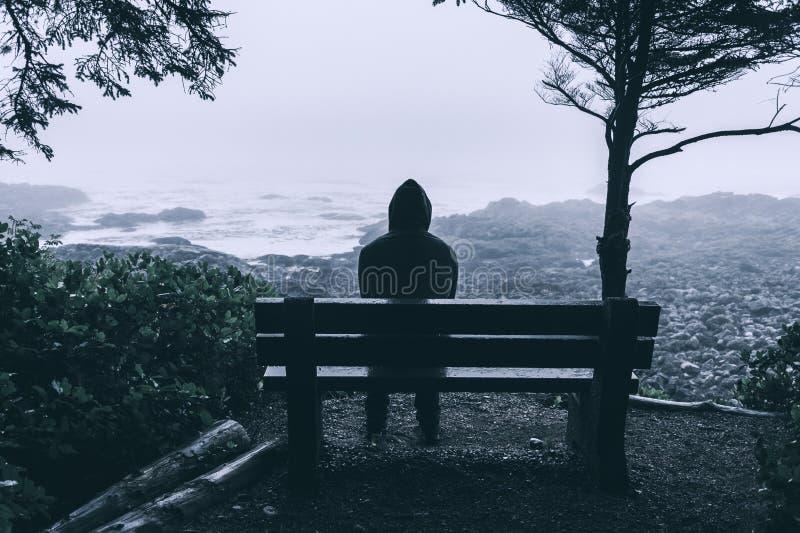 Συνεδρίαση ατόμων στον πάγκο στοκ φωτογραφίες