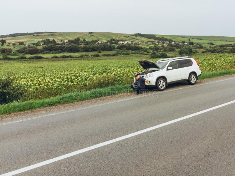 Συνεδρίαση ατόμων στο οδικό πλησίον σπασμένο αυτοκίνητο να δοκιμάσει το αυτοκίνητο στάσεων για τη βοήθεια στοκ εικόνα