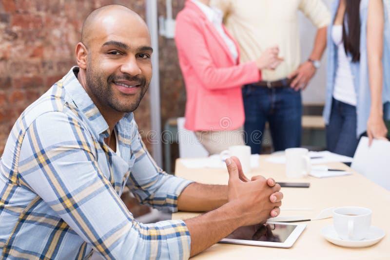 Συνεδρίαση ατόμων χαμόγελου στο γραφείο που χρησιμοποιεί την ταμπλέτα του στοκ φωτογραφίες