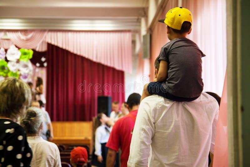 Συνεδρίαση γιων στους ώμους του πατέρα του στοκ φωτογραφία
