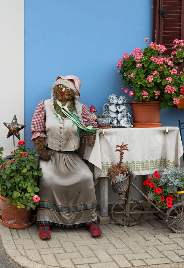 Συνεδρίαση γυναικείων αγροτών κουκλών αχύρου μπροστά από μια αγροικία, διακοπές Πάσχας, διακοσμήσεις στην Αυστρία στοκ φωτογραφία