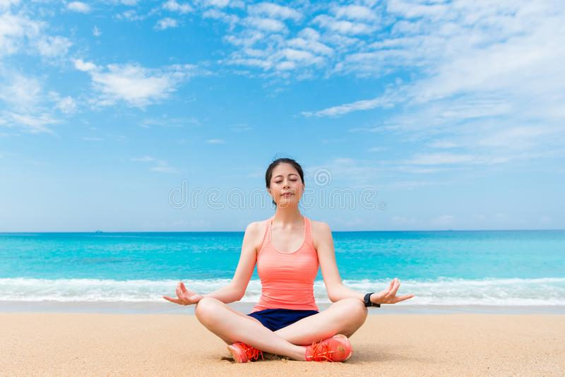 Συνεδρίαση γυναικών γιόγκας χαμόγελου όμορφη στην παραλία παραλιών στοκ φωτογραφία με δικαίωμα ελεύθερης χρήσης