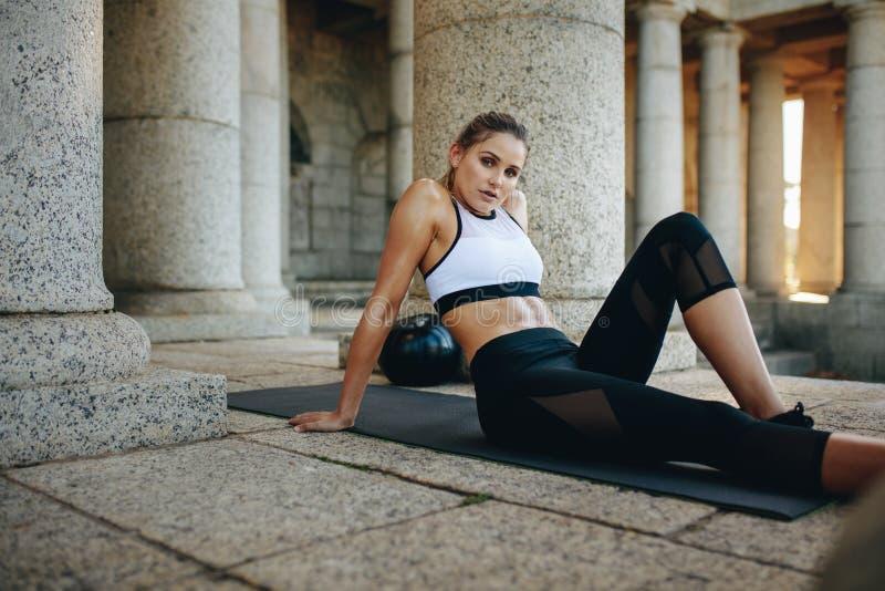 Συνεδρίαση γυναικών ικανότητας σε ένα χαλί γιόγκας και χαλάρωση κατά τη διάρκεια του workout στοκ φωτογραφίες