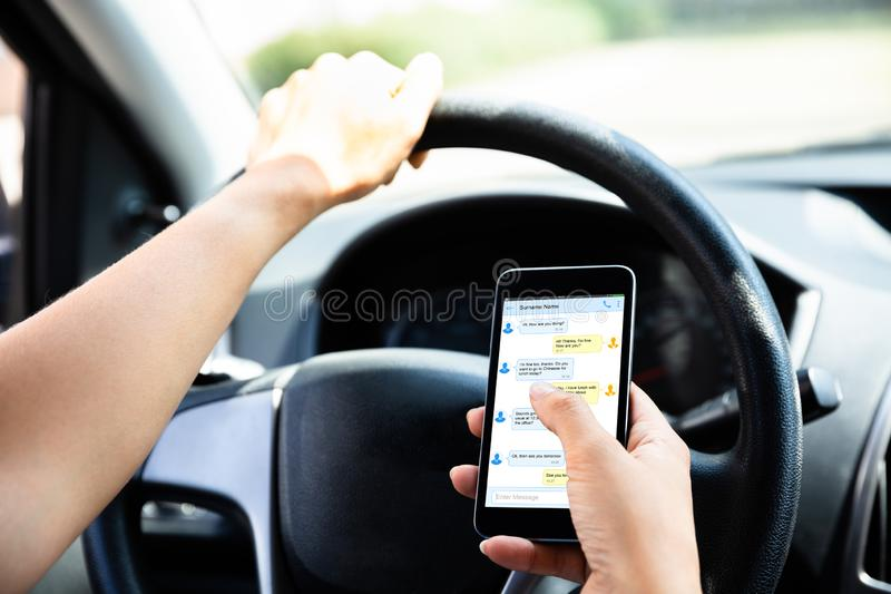Συνεδρίαση γυναικών μέσα στο μήνυμα κειμένου δακτυλογράφησης αυτοκινήτων στο κινητό τηλέφωνο στοκ φωτογραφία με δικαίωμα ελεύθερης χρήσης