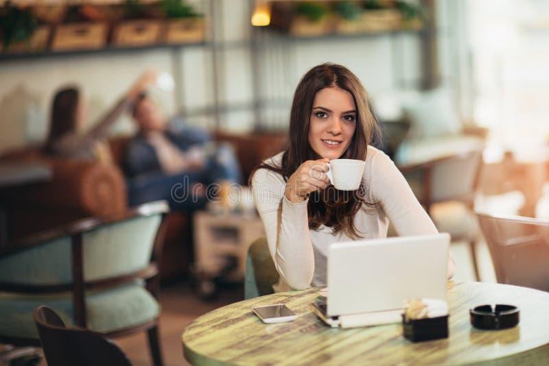 Συνεδρίαση γυναικών μπροστά από τον ανοικτό φορητό προσωπικό υπολογιστή στο φραγμό καφέδων στοκ φωτογραφίες