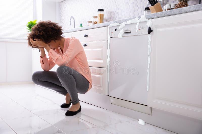 Συνεδρίαση γυναικών μπροστά από το χαλασμένο πλυντήριο πιάτων στοκ φωτογραφίες