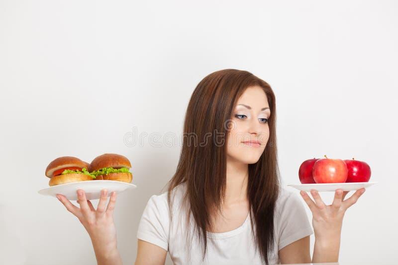Συνεδρίαση γυναικών πίσω από τον πίνακα με τα τρόφιμα στοκ εικόνες