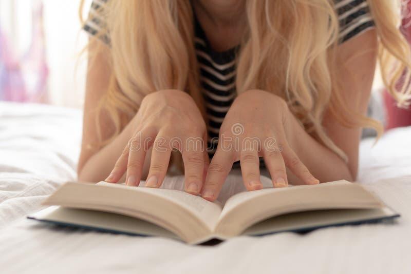 Συνεδρίαση γυναικών που χαλαρώνουν στη χάντρα που διαβάζει ένα βιβλίο στοκ εικόνες