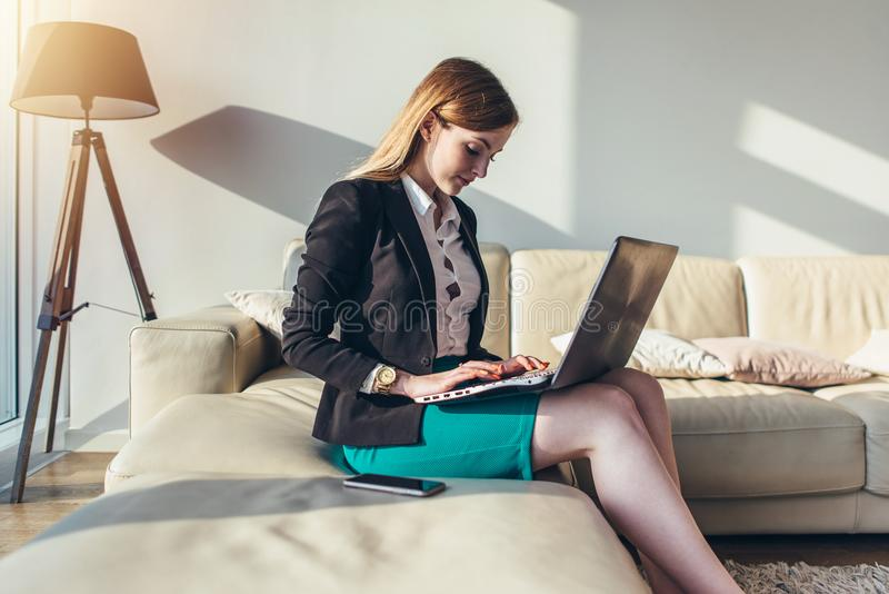 Συνεδρίαση γυναικών σε έναν καναπέ με ένα lap-top στη δακτυλογράφηση περιτυλίξεών της στο πληκτρολόγιο στο σπίτι στοκ φωτογραφίες