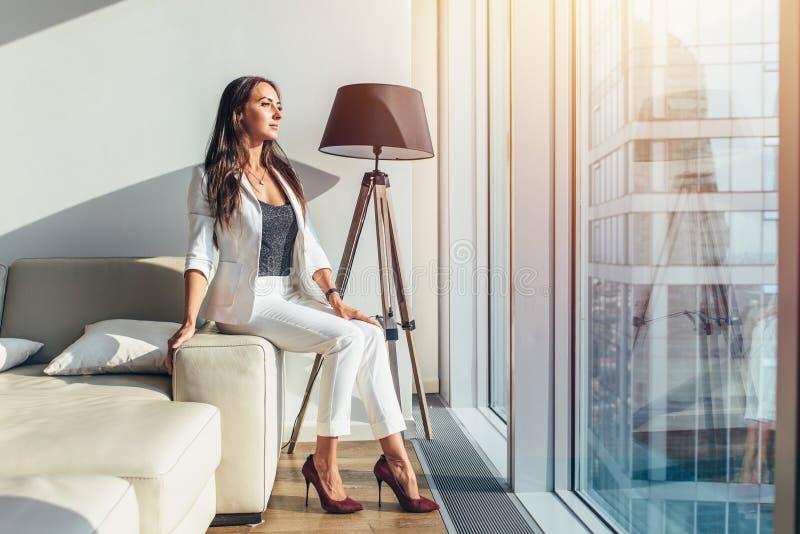 Συνεδρίαση γυναικών σε έναν καναπέ στο σύγχρονο διαμέρισμα στοκ φωτογραφίες με δικαίωμα ελεύθερης χρήσης