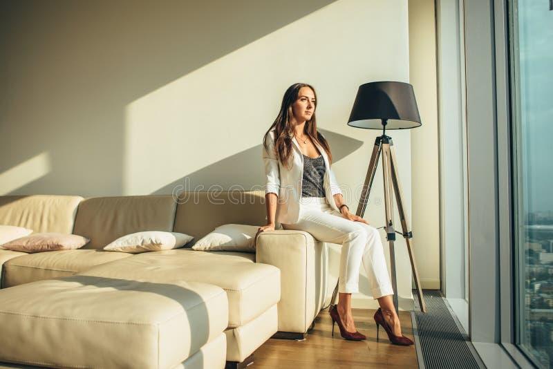 Συνεδρίαση γυναικών σε έναν καναπέ στο σύγχρονο διαμέρισμα στοκ εικόνες με δικαίωμα ελεύθερης χρήσης