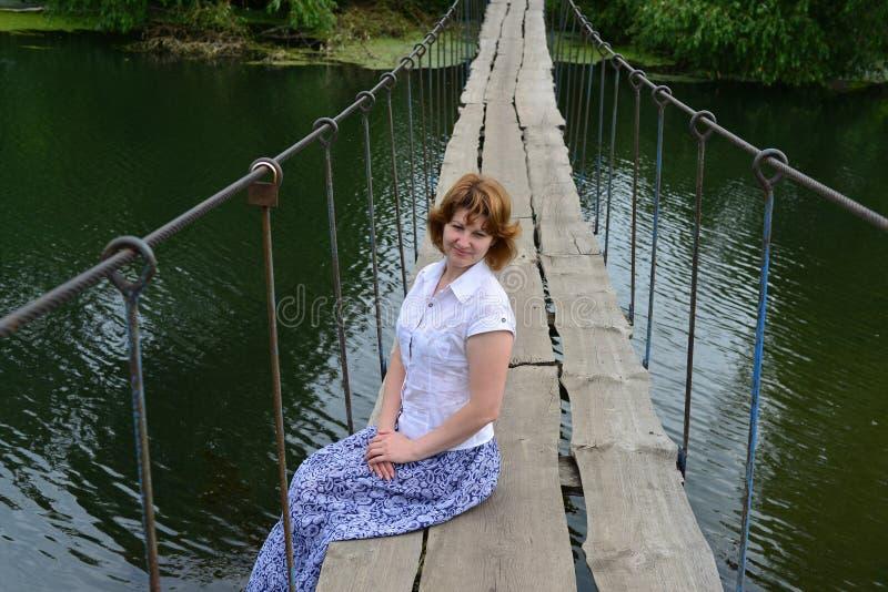 Συνεδρίαση γυναικών σε μια ξύλινη γέφυρα πέρα από τον ποταμό στοκ εικόνα με δικαίωμα ελεύθερης χρήσης