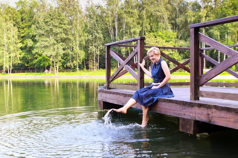 Συνεδρίαση γυναικών σε μια ξύλινη πρόσδεση πέρα από το νερό με τα πόδια της στο νερό στοκ εικόνα