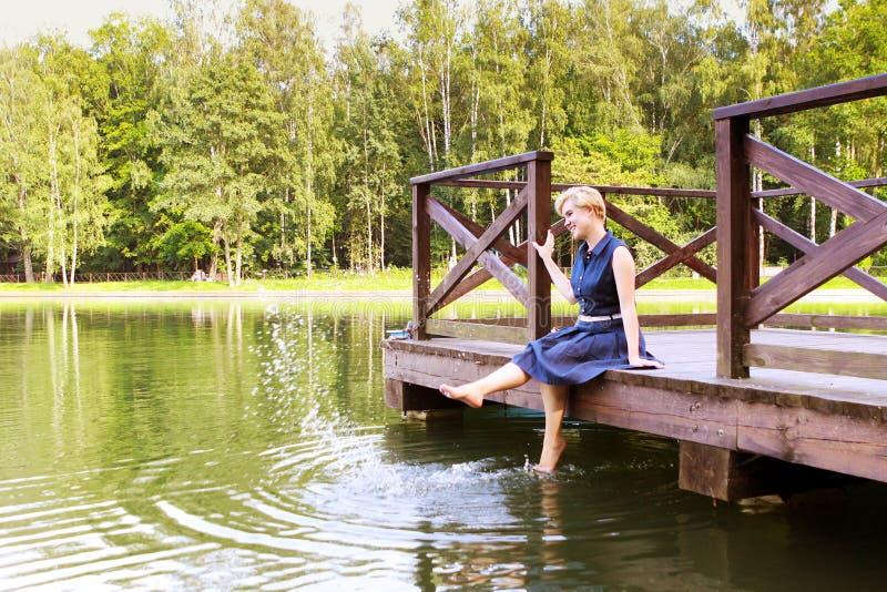 Συνεδρίαση γυναικών σε μια ξύλινη πρόσδεση πέρα από το νερό με τα πόδια της στο νερό Θερινές διακοπές κοντά στο νερό στοκ εικόνες