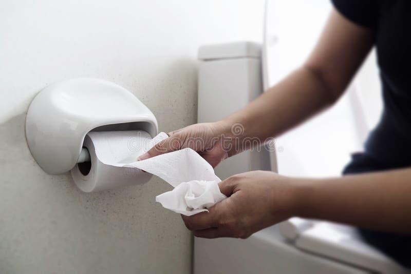Συνεδρίαση γυναικών σε χαρτί ιστού εκμετάλλευσης κύπελλων τουαλετών - έννοια προβλήματος υγείας στοκ εικόνα