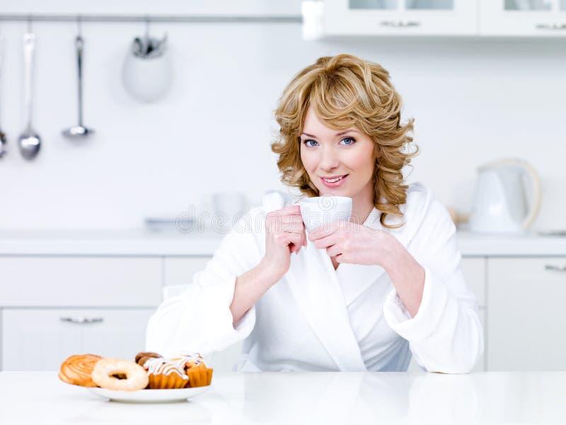 Συνεδρίαση γυναικών στην κουζίνα και τον καφέ κατανάλωσης στοκ εικόνα